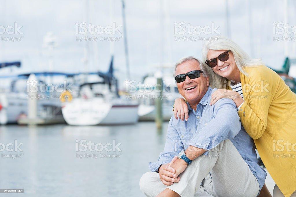 Happy senior couple enjoying harbor view stock photo