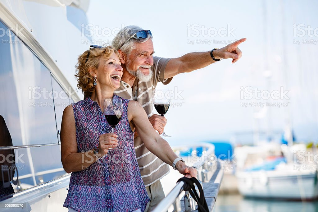 Happy senior couple enjoying wine on yacht stock photo