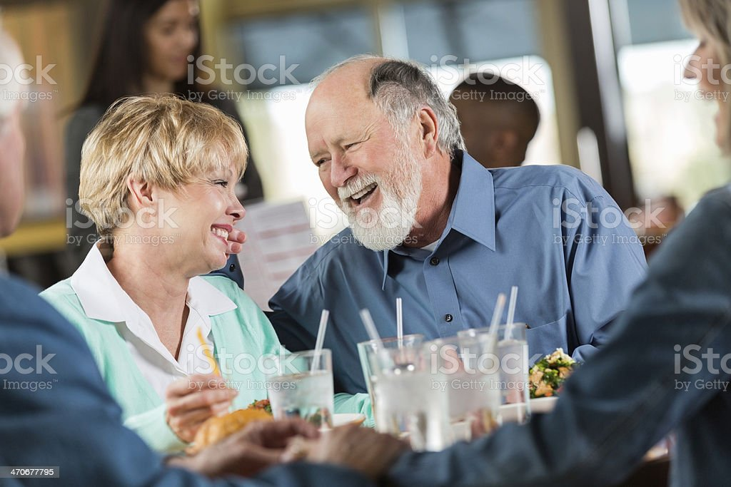 Happy senior couple having meal with friends in modern restaurant stock photo