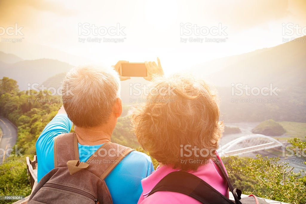 happy Senior couple hiking on mountains and taking selfies stock photo