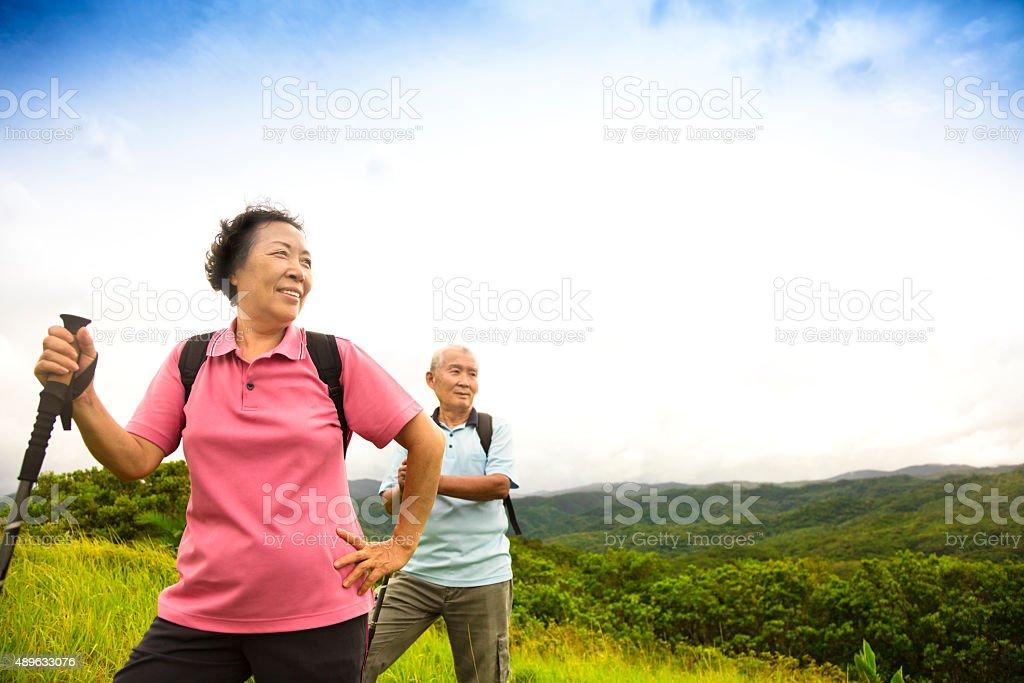 happy senior couple hiking on the mountain stock photo
