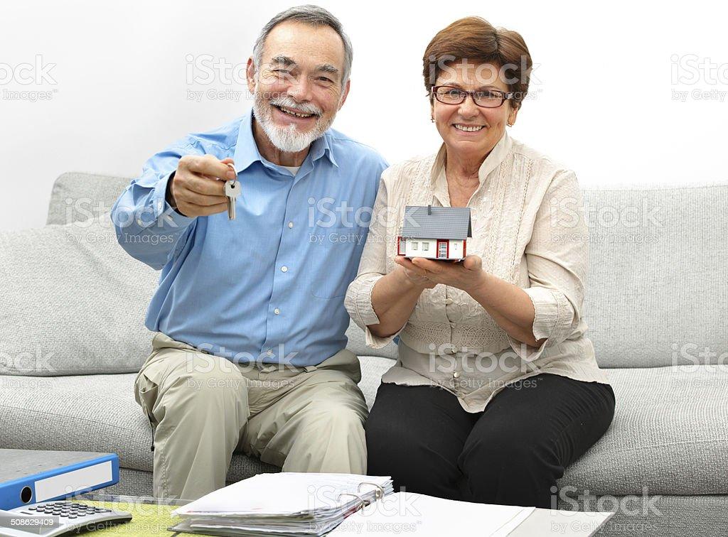 Happy senior couple holding a small house stock photo