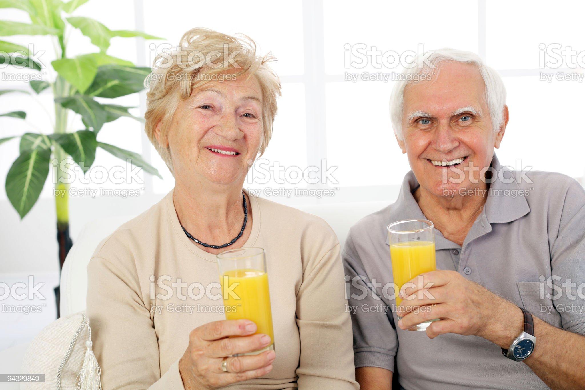 Happy senior couple holding glasses with juice. royalty-free stock photo