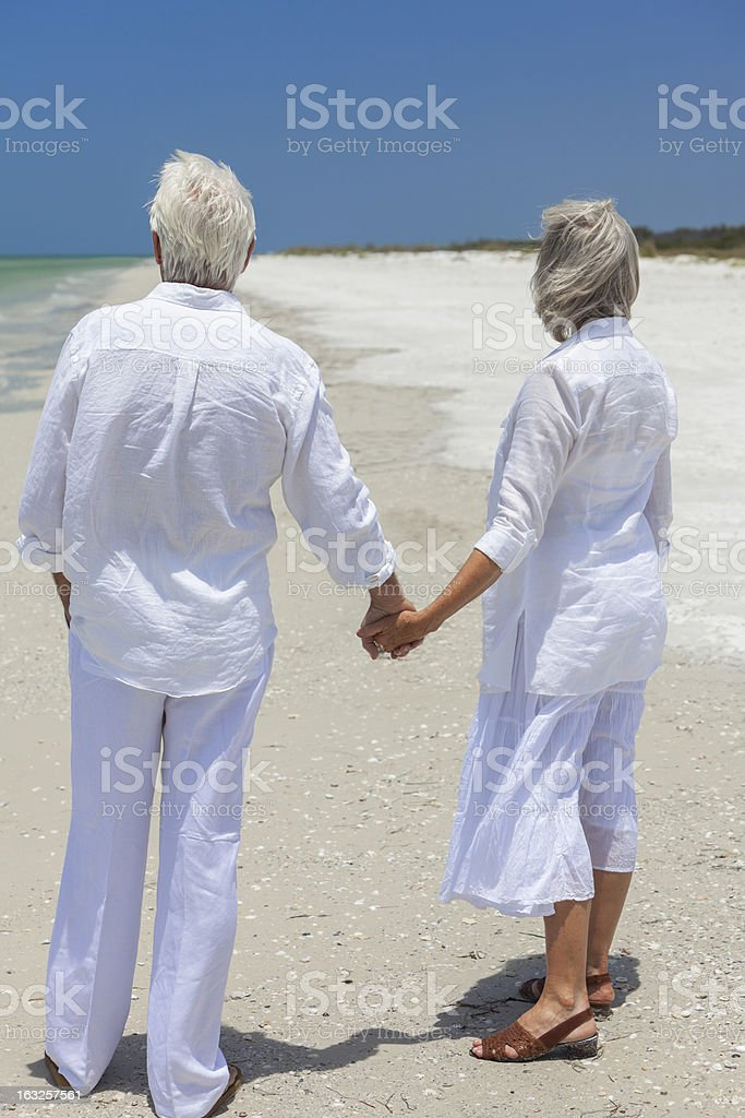 Happy Senior Couple Holding Hands on Tropical Beach royalty-free stock photo