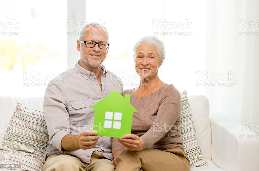happy senior couple hugging on sofa at home stock photo