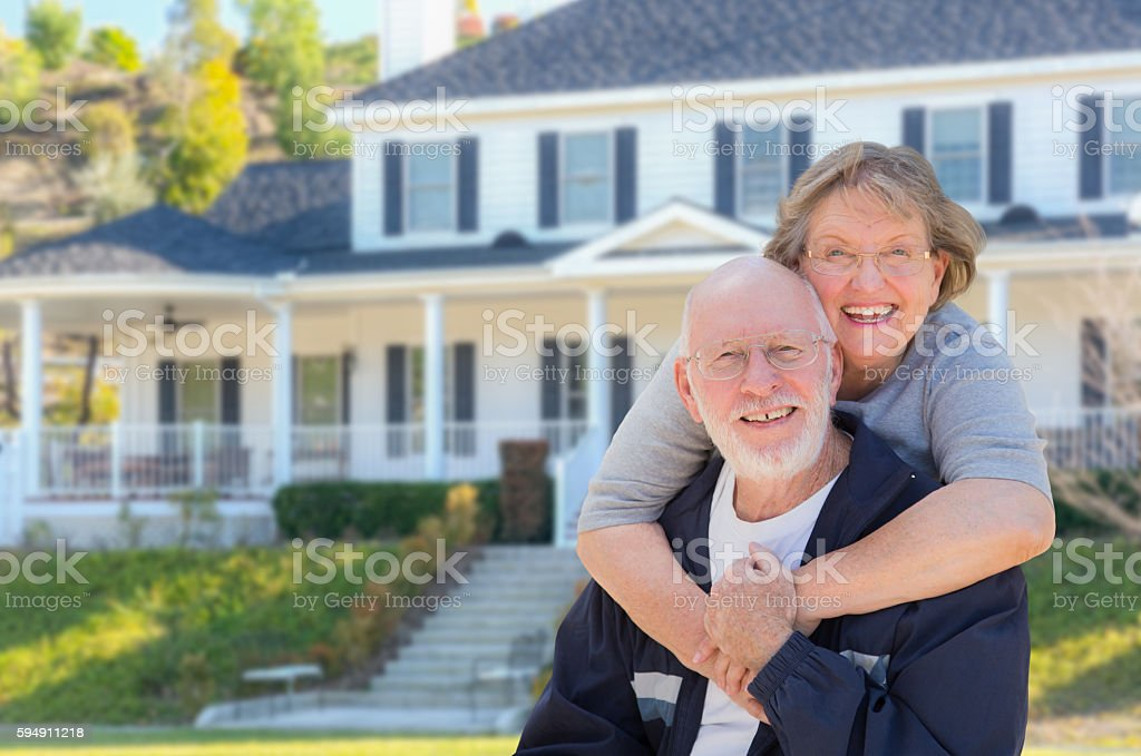 Happy Senior Couple in Front of House stock photo