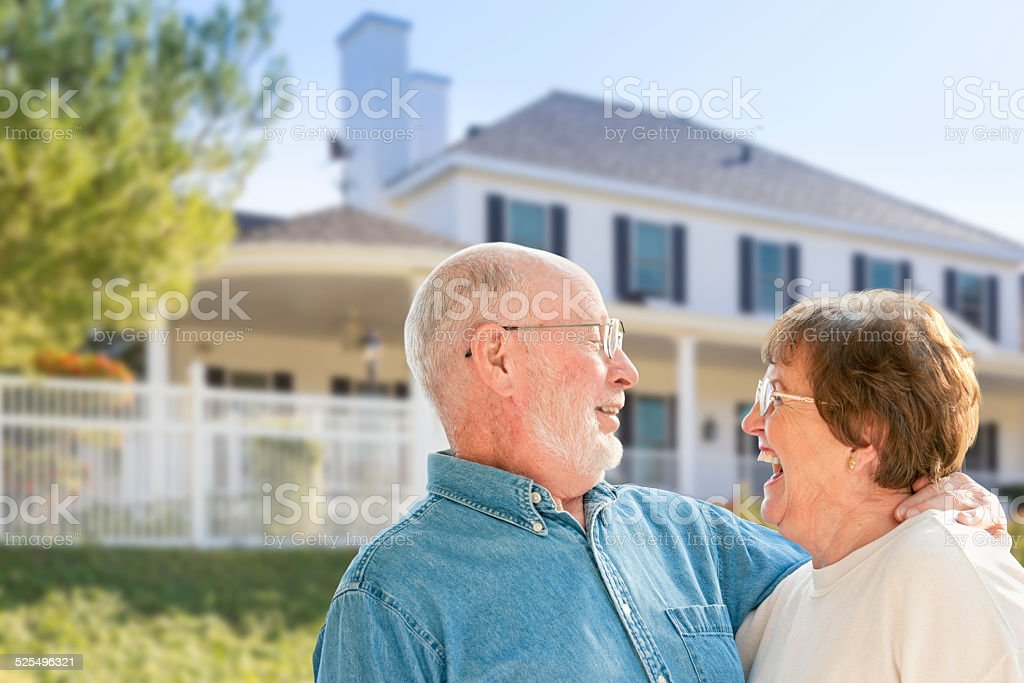Happy Senior Couple in Front Yard of House stock photo