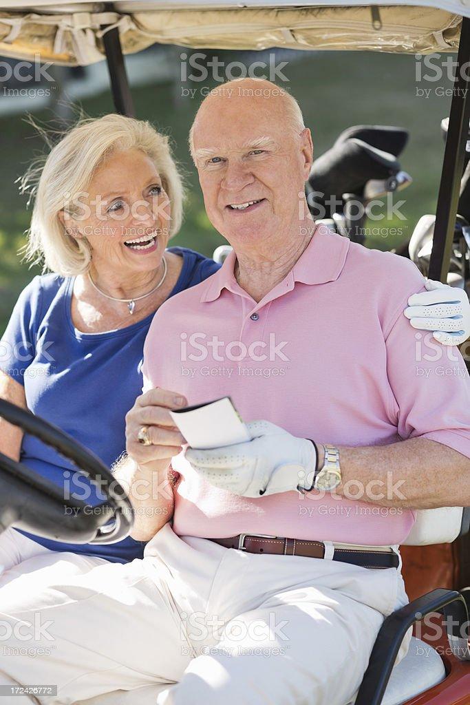 Happy Senior Couple In Golf Cart royalty-free stock photo