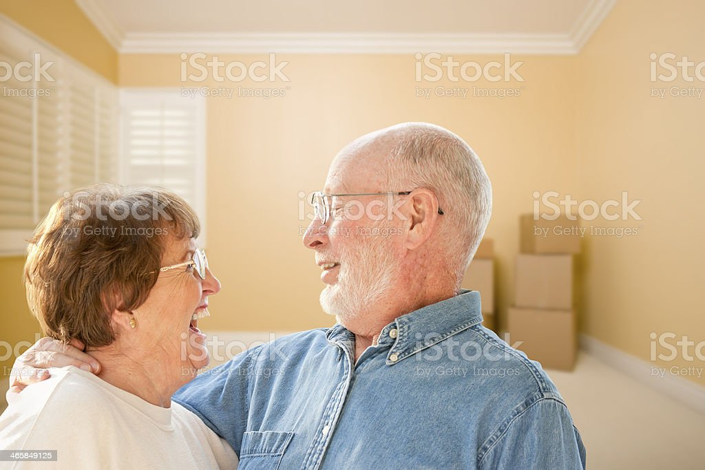 Happy Senior Couple In Room with Moving Boxes on Floor stock photo