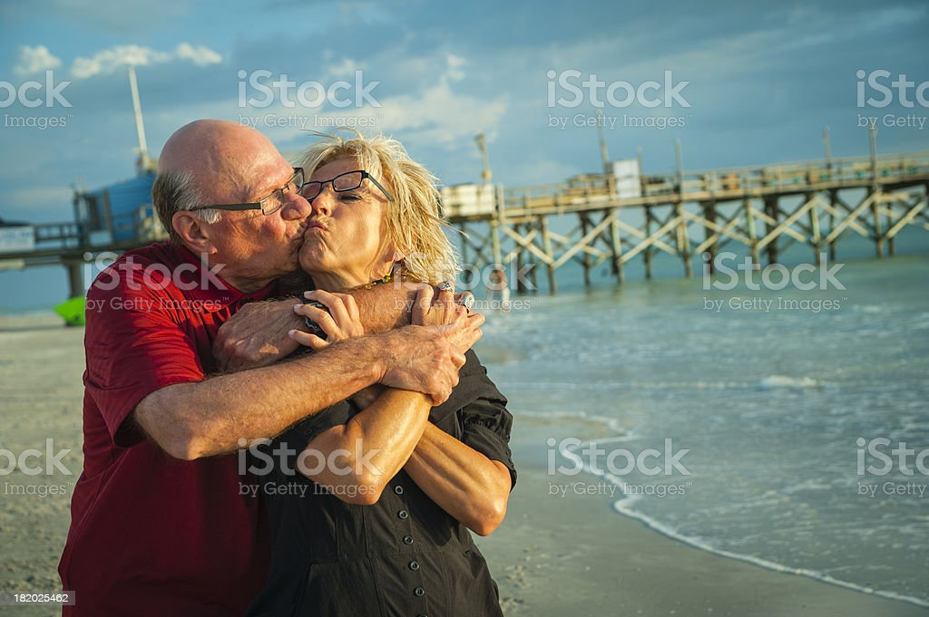 Happy senior couple kissing on the beach at sunset. royalty-free stock photo