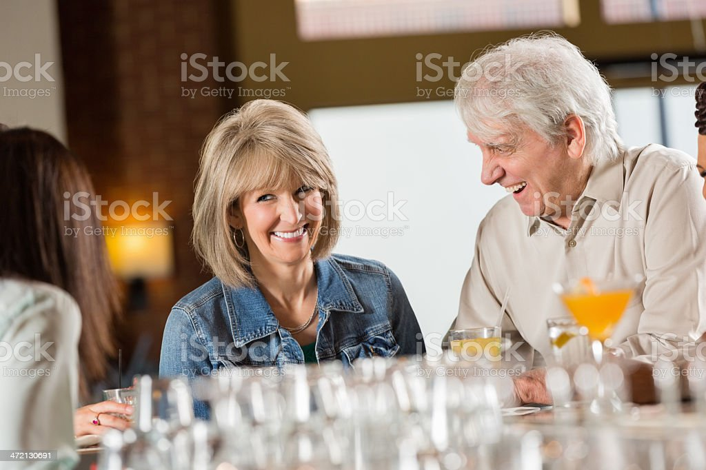 Happy senior couple laughing together while having drinks at bar royalty-free stock photo