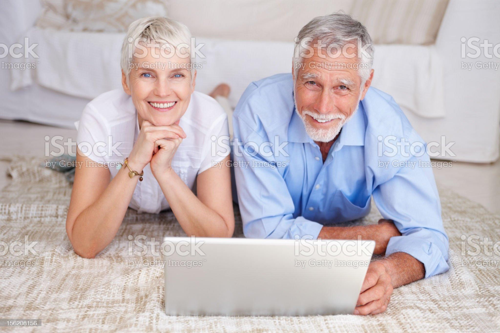 Happy senior couple lying on floor with laptop royalty-free stock photo