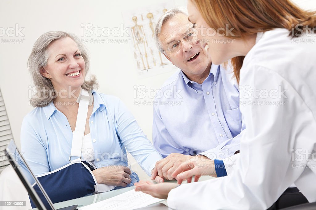 Happy Senior Couple Meeting With Their Doctor royalty-free stock photo