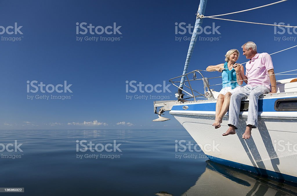 Happy Senior Couple on the Bow of a Sail Boat stock photo
