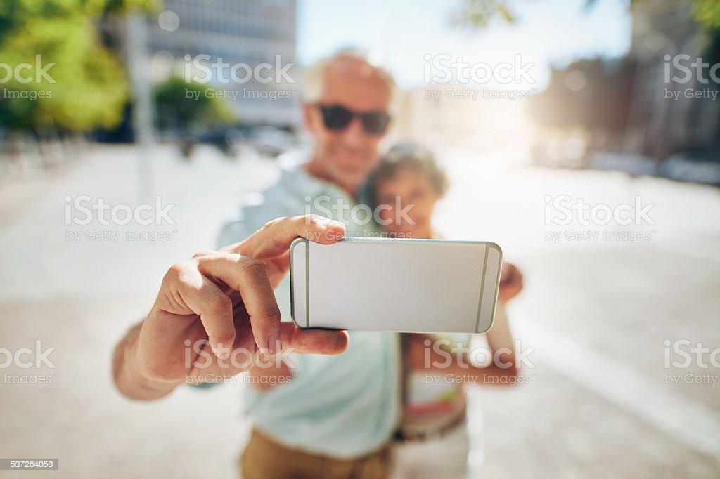 Happy senior couple on vacation taking a selfie stock photo
