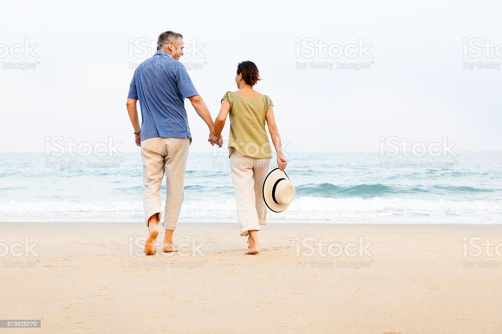 Happy senior couple outdoors on the beach stock photo