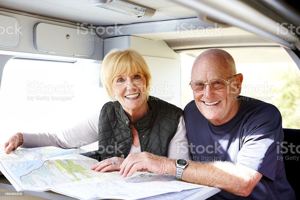 Happy senior couple planning for a roadtrip royalty-free stock photo