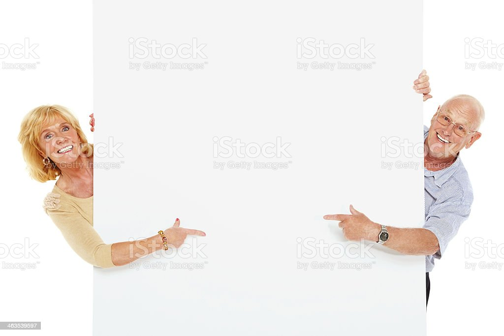 Happy senior couple pointing at blank billboard royalty-free stock photo