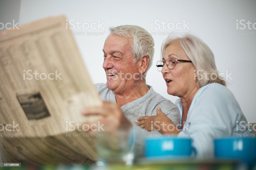 Happy senior couple reading newspaper in the morning stock photo