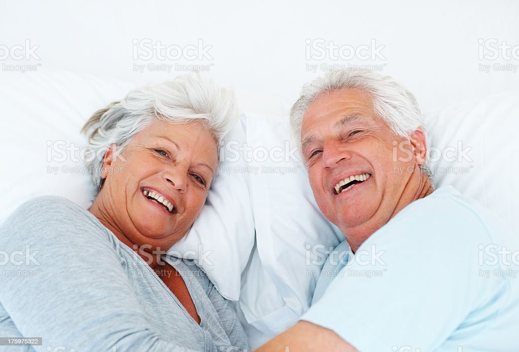 Happy senior couple relaxing in bed stock photo