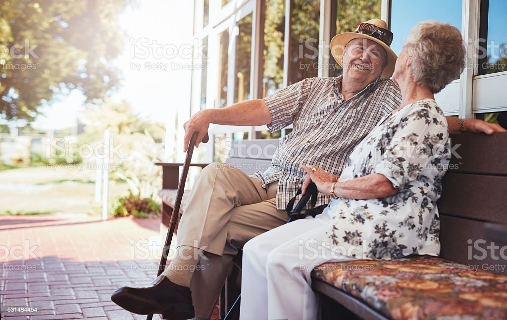 Happy senior couple relaxing on bench outside their house stock photo