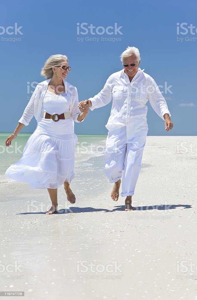 Happy Senior Couple Running Holding Hands on A Tropical Beach royalty-free stock photo