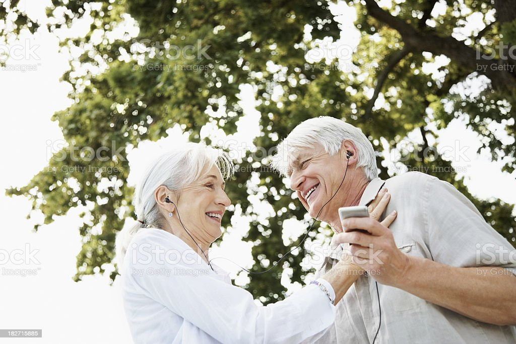 Happy Senior Couple Sharing an Audio Player Outdoors stock photo