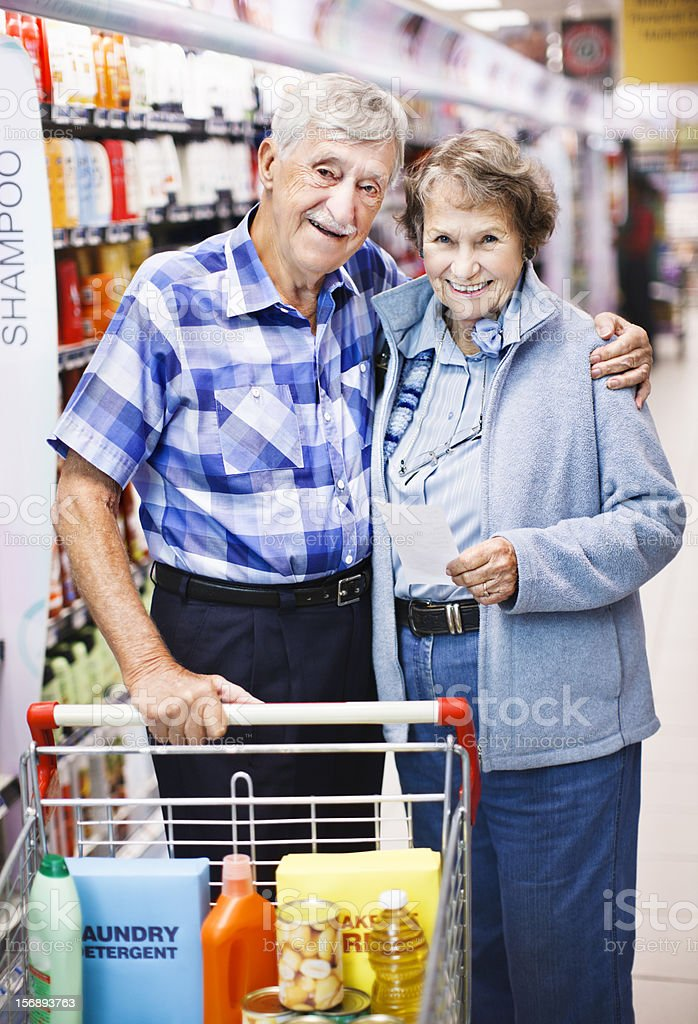 Happy senior couple shopping in the supermarket stock photo