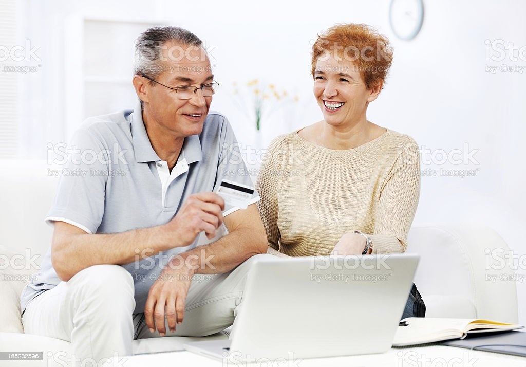 Happy senior couple shopping online royalty-free stock photo