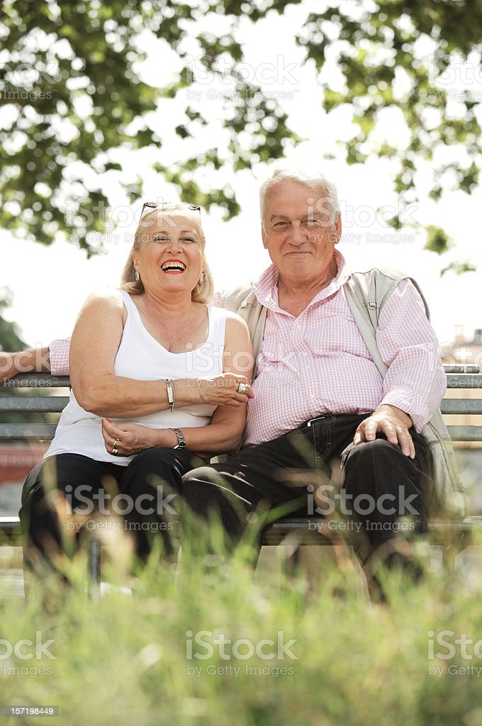 Happy senior couple sitting in the park royalty-free stock photo