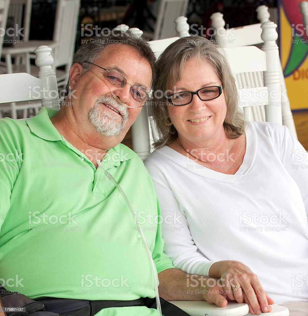 Happy senior couple sitting in white wooden chairs stock photo