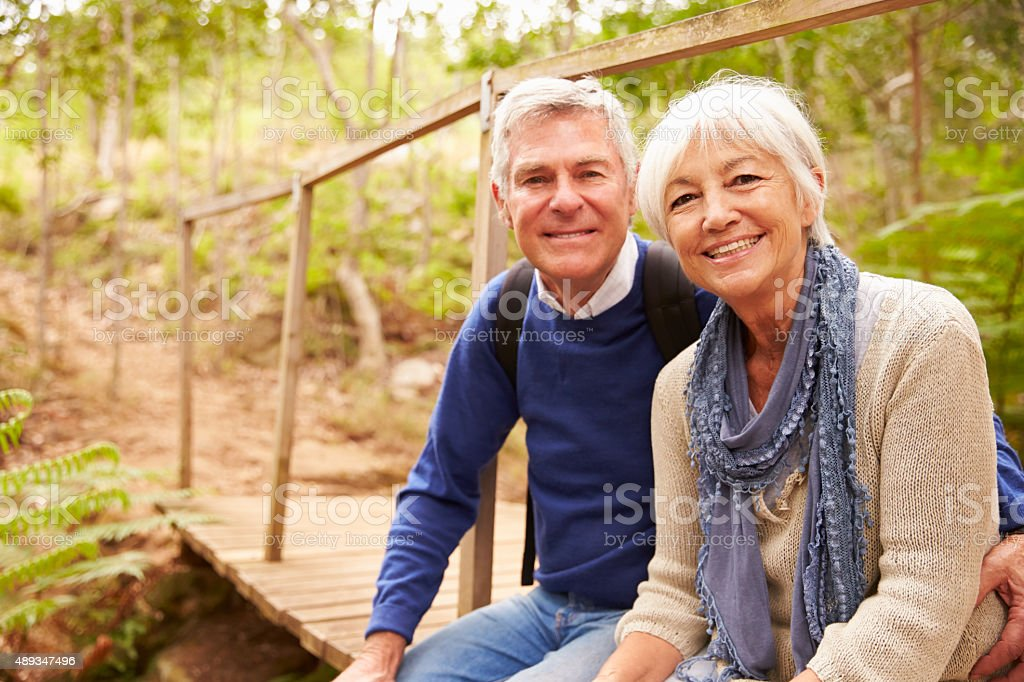 Happy senior couple sitting on a bridge in forest, portrait stock photo