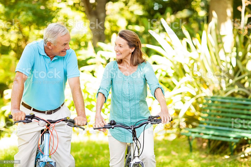 Happy Senior Couple Sitting On Bicycles In Park stock photo