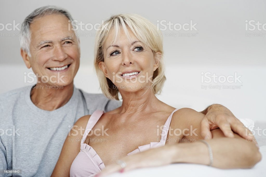 Happy senior couple sitting on sofa and looking away royalty-free stock photo