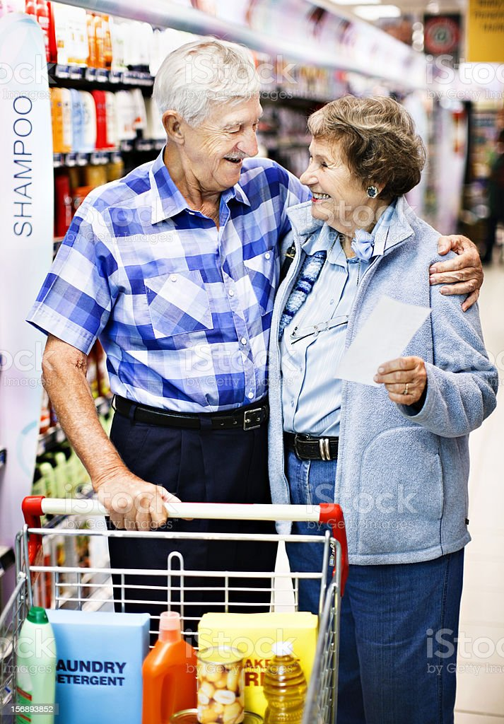 Happy senior couple smile, hug, while shopping in supermarket stock photo