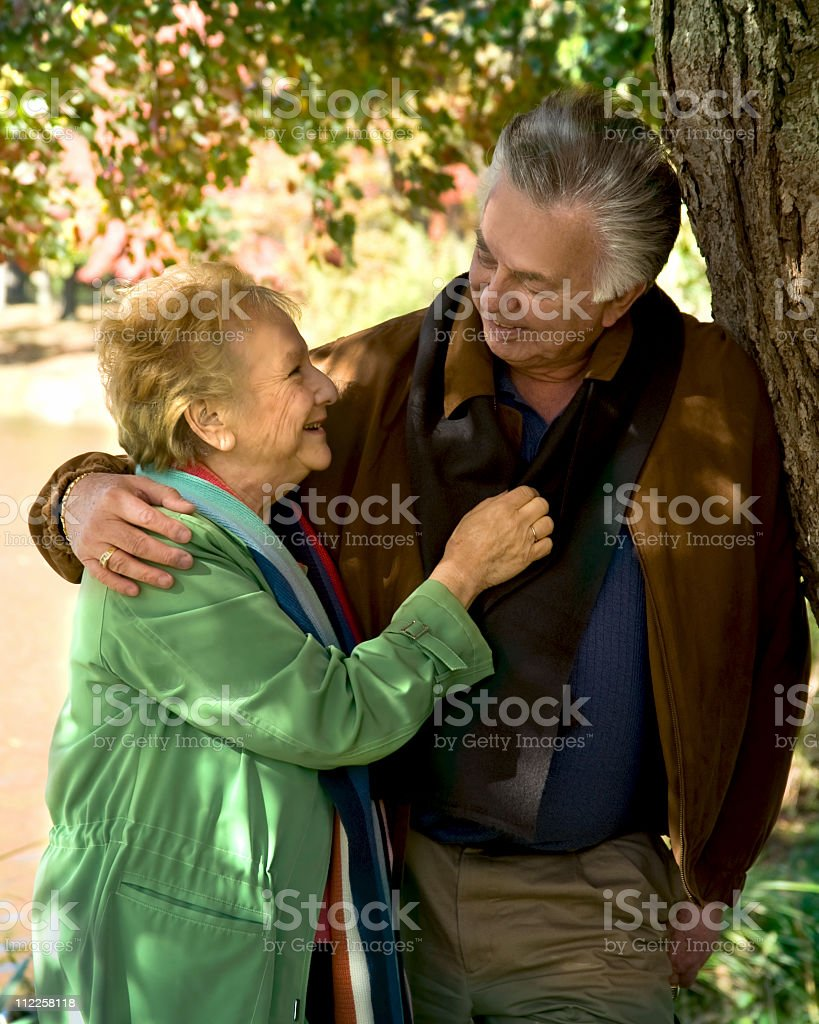 Happy senior couple smiling in the park royalty-free stock photo