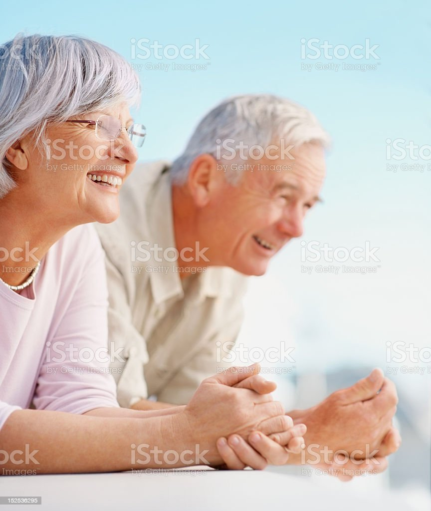 Happy senior couple standing at the balcony royalty-free stock photo
