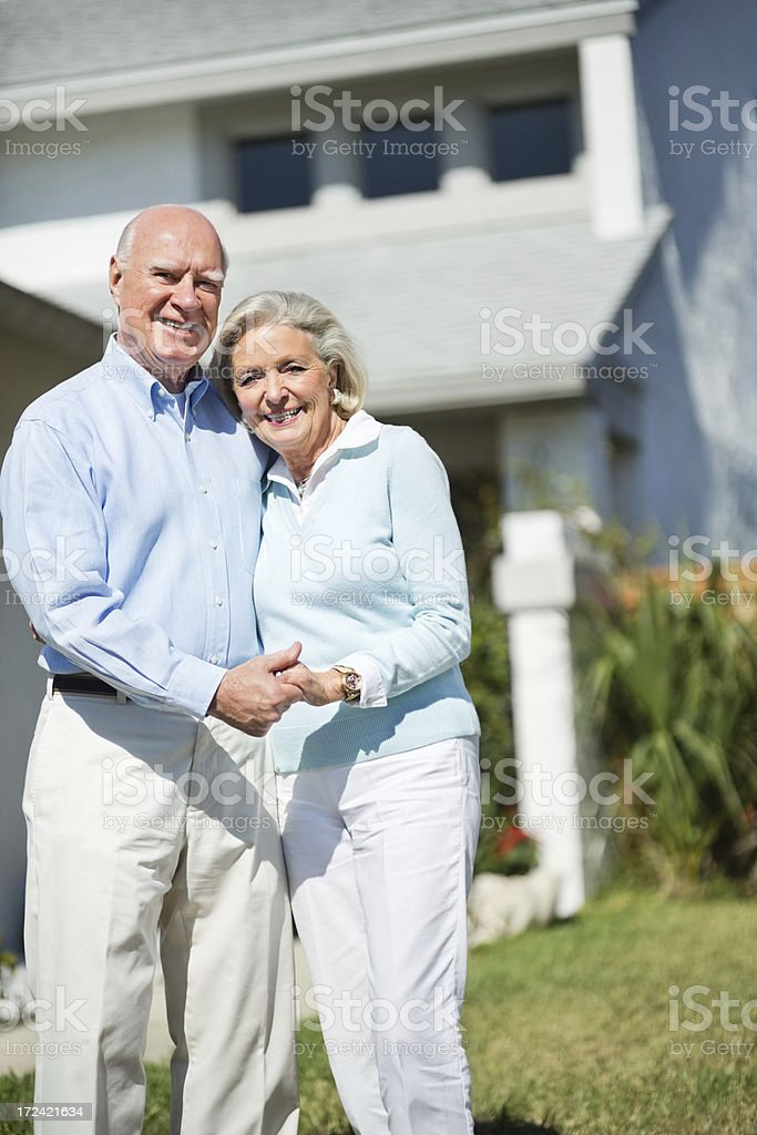 Happy Senior Couple Standing In Lawn royalty-free stock photo