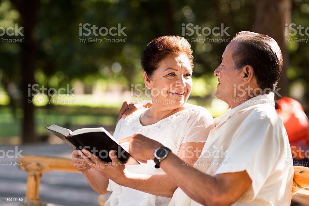 Happy senior couple studying the Bible stock photo