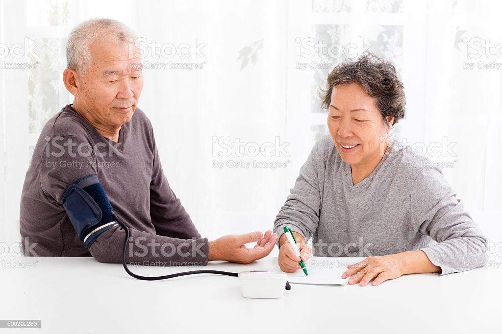 happy Senior couple taking  blood pressure in living room stock photo