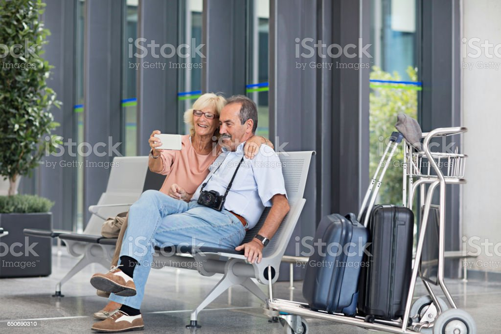 Happy senior couple taking selfie in airport stock photo