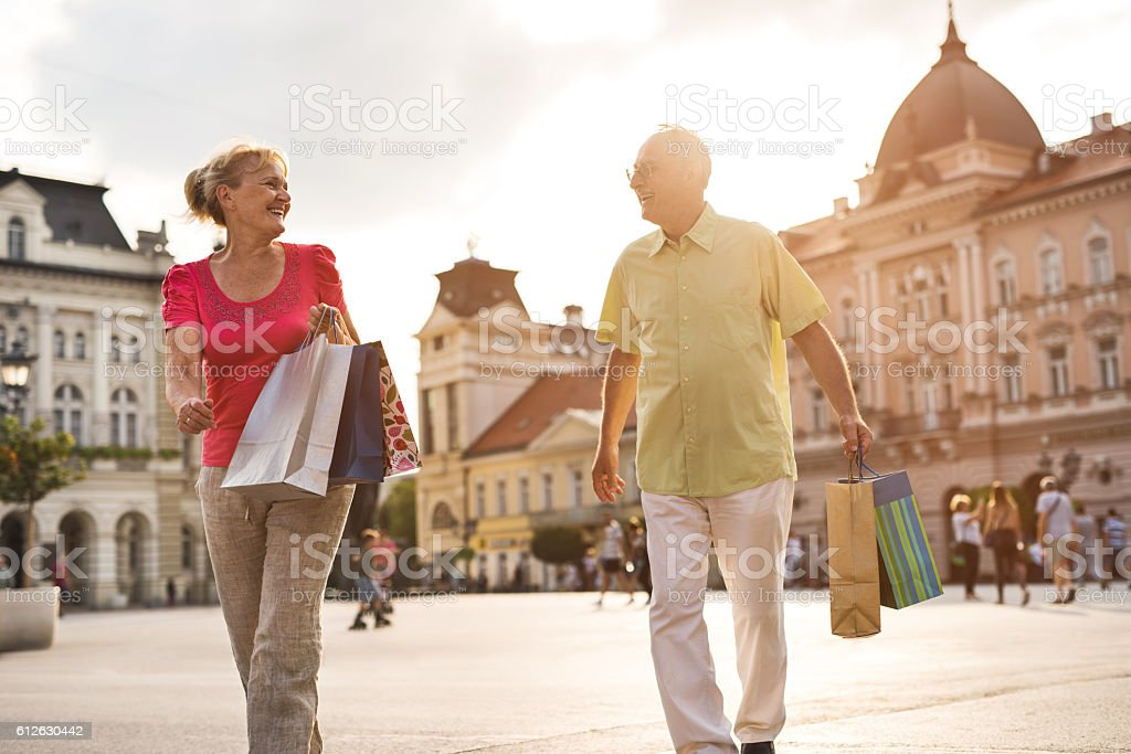 Happy senior couple talking while shopping in the city. stock photo