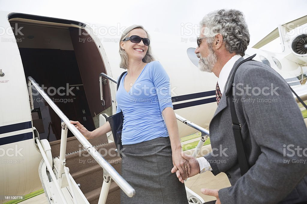 Happy senior couple travelling by private jet together royalty-free stock photo