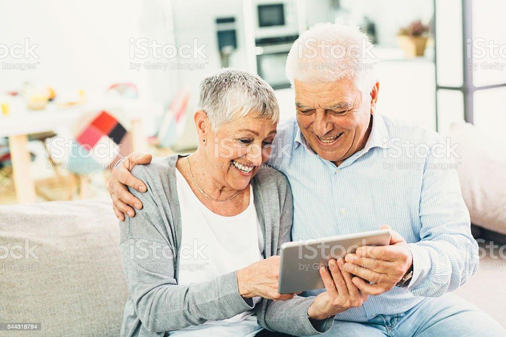 Happy senior couple using a tablet stock photo