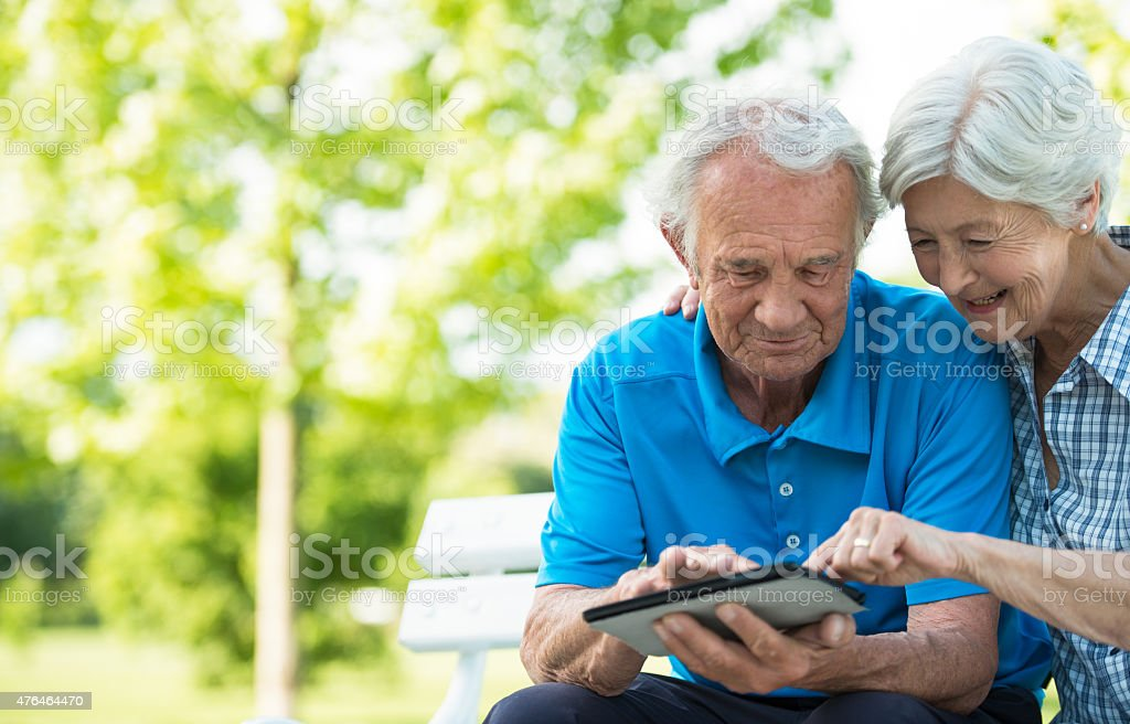 Happy senior couple using digital tablet in park. stock photo