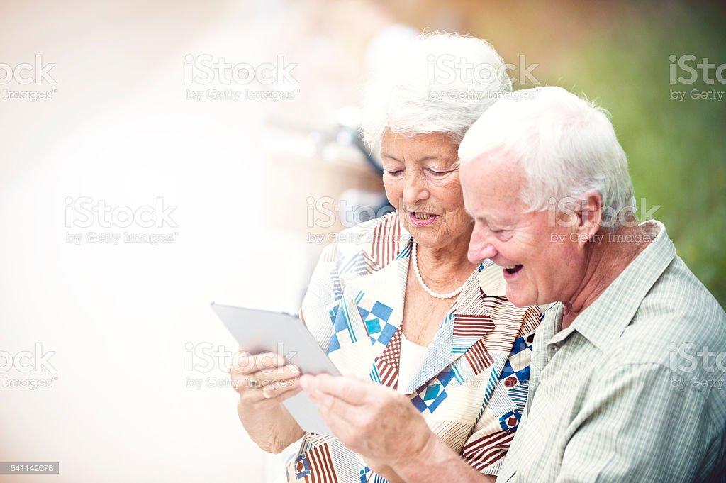 Happy senior couple using digital tablet in park stock photo