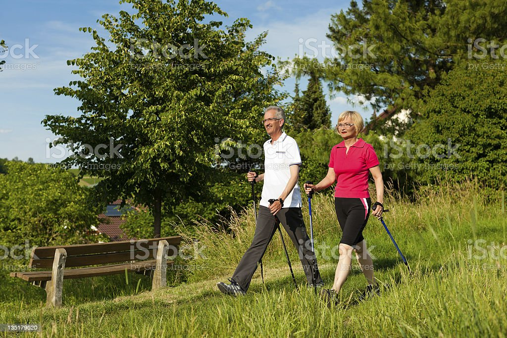 Happy senior couple walking at a park stock photo