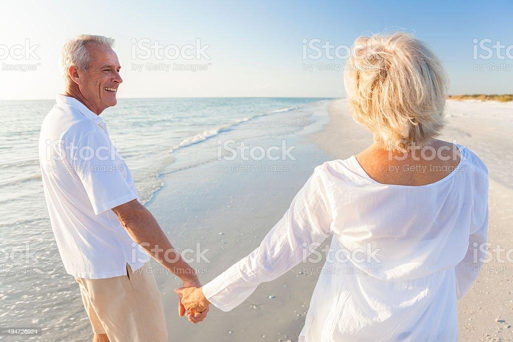 Happy Senior Couple Walking Holding Hands Tropical Beach stock photo