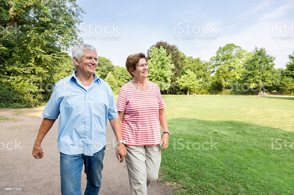 Happy senior couple walking outdoors in the park stock photo