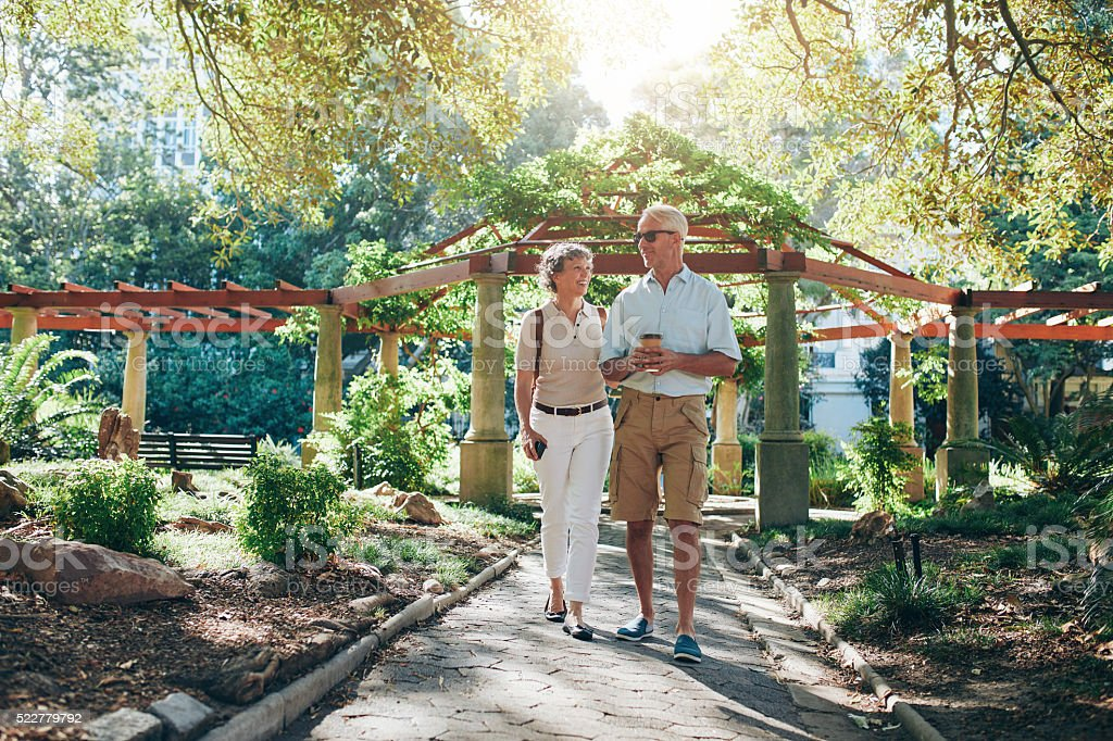 Happy senior couple walking together in a city park stock photo